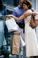 Young couple looking through a shop window