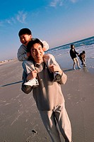 Father carrying his son on his shoulders walking on the beach