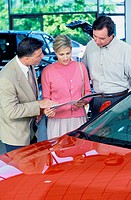 Mid adult couple looking at a brochure in a car showroom