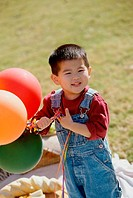 Portrait of a boy holding balloons (thumbnail)