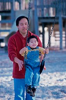 Father pushing his son on a swing