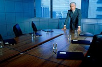 Businessman leaning on a conference table (thumbnail)