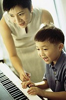 Mother teaching her son the piano