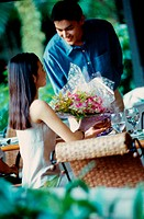 Young man giving a bouquet of flowers to a young woman