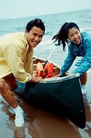 Young couple pulling a canoe on the beach