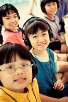 Portrait of a group of children wearing headphones smiling (thumbnail)