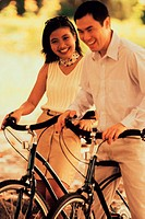 Young couple standing with bicycles