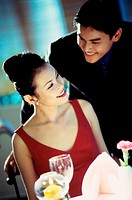 Young couple smiling at each other at a dining table