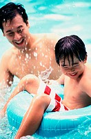 Father with his son playing in a swimming pool
