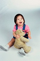 Baby girl playing with a teddy bear