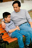 Father and son sitting on a park bench