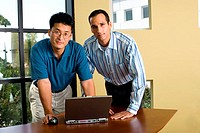 Portrait of two businessmen standing in front of a laptop