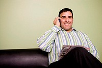 Portrait of a businessman sitting on a couch talking on a mobile phone