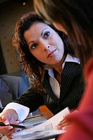 Side profile of two businesswomen sitting in a conference room