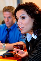 Close-up of a businesswoman and a businessman sitting in a conference room