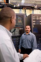 Two technicians talking in front of a network server