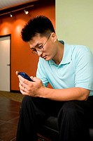 Businessman sitting in an office holding a mobile phone