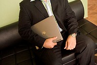 Mid section view of a businessman sitting on a couch holding a laptop