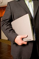 Mid section view of a businessman holding a laptop