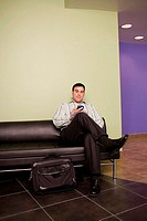 Businessman sitting in an office working on a palmtop