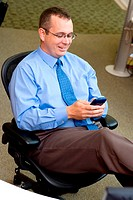 Businessman sitting in an office holding a palmtop