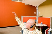 Male customer service representative wearing a headset with his hand raised