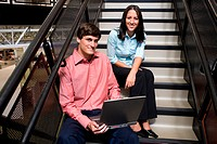 Portrait of a businessman and a businesswoman sitting on stairs in front of a laptop