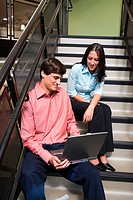 Businessman and a businesswoman sitting on stairs in front of a laptop