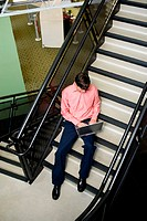 High angle view of a businessman sitting on stairs working on a laptop