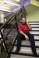Businessman sitting on stairs talking on a mobile phone