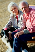Portrait of a senior couple sitting with their dog