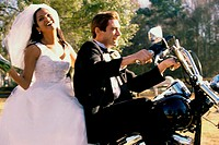 Newlywed couple riding on a motorcycle (thumbnail)