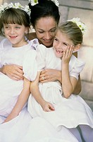 Bride hugging two flower girls