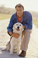 Portrait of a mid adult man hugging his dog (thumbnail)