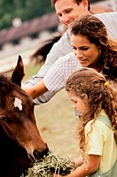 Girl feeding a horse with her parents (thumbnail)