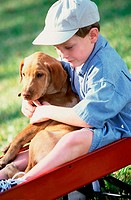 Boy sitting in a toy wagon holding his dog