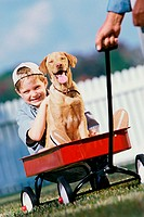 Portrait of boy sitting in a toy wagon with his dog