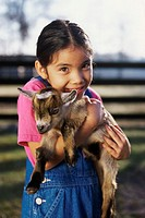 Portrait of a girl holding a kid goat in her arms