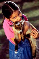 High angle view of a girl holding a kid goat in her arms