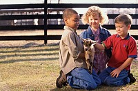 Three children holding a goat