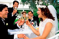 Newlywed couple and their friends toasting with champagne glasses