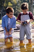Two boys standing in water holding a turtle