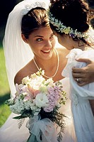 Close-up of a bride smiling at a flower girl