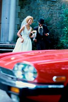 Newlywed couple running towards a car