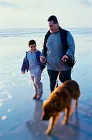 Father and his son walking with their dog on the beach