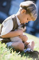 Side profile of a boy holding a Siamese kitten