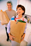 Mid adult couple standing in a kitchen holding grocery bags