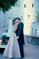 Newlywed couple kissing each other in front of an antique car