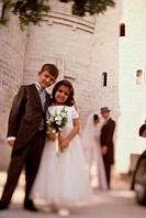 Portrait of a ring bearer and a flower girl standing in front of a church