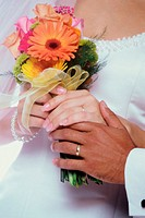 Bride and groom holding a bouquet of flowers together